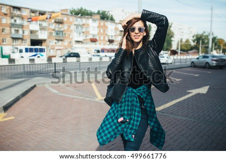 Urban fashionable girl posing in a leather jacket outdoors in the city
