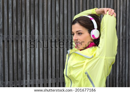 Urban fitness woman stretching arms triceps on fitness working out and exercising outside. Sporty woman exercising outside wearing headphones and outfit sportswear. - stock photo