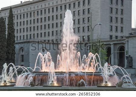 Urban fountain illuminated at sunset - stock photo