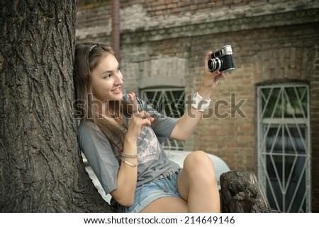 Urban girl has fun with vintage photo cameras outdoor near tree, image toned. - stock photo