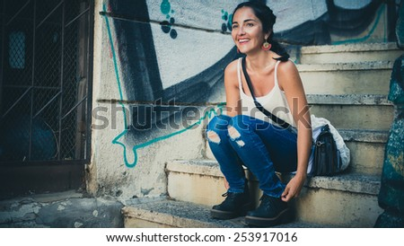 Urban girl sitting in the middle of the city. - stock photo