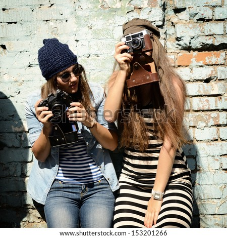 urban girls have fun with vintage photo cameras outdoor near grunge wall, image toned and noise added - stock photo