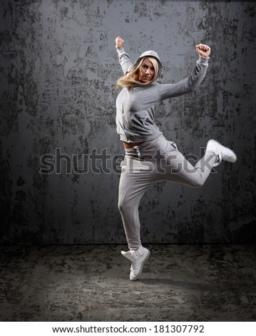 Urban hip hop dancer jumping and dancing with hoodie  - stock photo