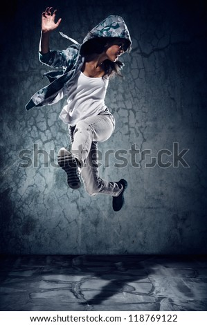 urban hip hop dancer with grunge concrete wall background texture jumping and dancing with hoodie