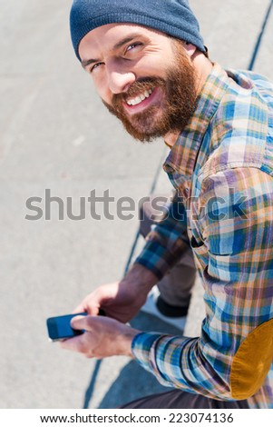 Urban lifestyle. Top view of handsome young man sitting and writing a message  - stock photo