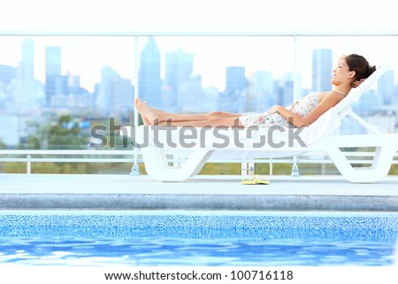 Urban luxury city lifestyle woman lying by pool relaxing in sun lounger during summer in Montreal, Quebec, Canada.