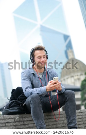 Urban man on smart phone wearing headphones listening to music or having video chat conversation sitting outside using app on 4g smartphones. Casual young urban professional male in Hong Kong Central. - stock photo