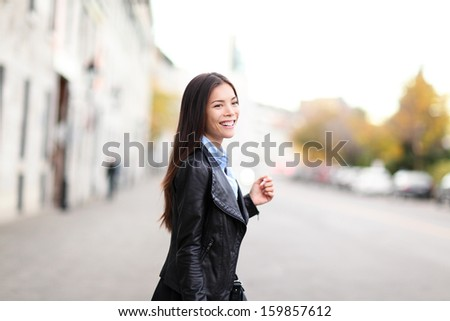Urban modern woman outdoor walking in street. Female fashion model wearing cool leather jacket crossing the road outside. Happy mixed race Asian Caucasian girl in her twenties. - stock photo