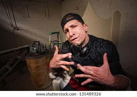Urban musician with crossed fingers and goofy expression - stock photo