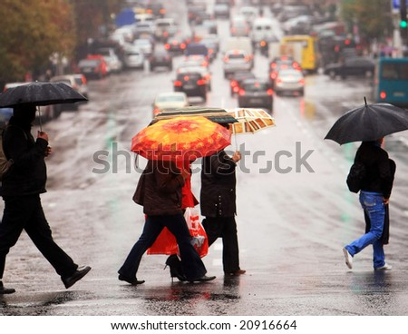 urban people cross the street on the rain