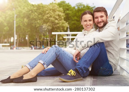 urban photo of smiley young couple sitting and looking at camera - stock photo