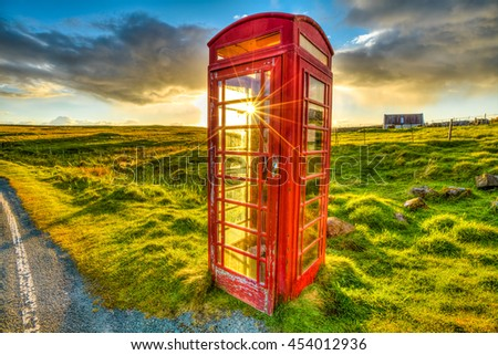 Urban red telephone box in the middle of a green countryside. Concept for synergy between modern and rural area. Red and green complementary colors join together in a scottish land, United Kingdom. - stock photo