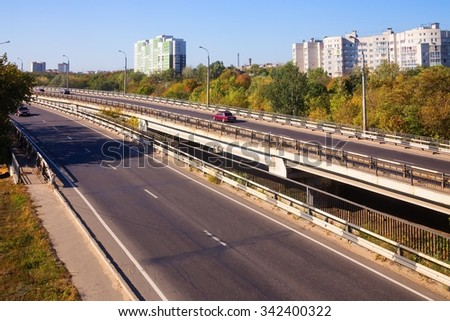 Urban road against background of high-rise buildings in autumn - stock photo