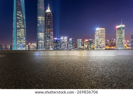 urban road,illuminated skyline background