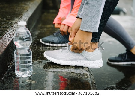 Urban running and fitness workout outdoor under the rain concept. Female athletes lacing sport shoes on wet stairs. - stock photo
