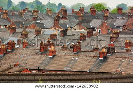 Urban scene across built up residential area of terraced houses showing the slate roof tops of an old housing estate - stock photo