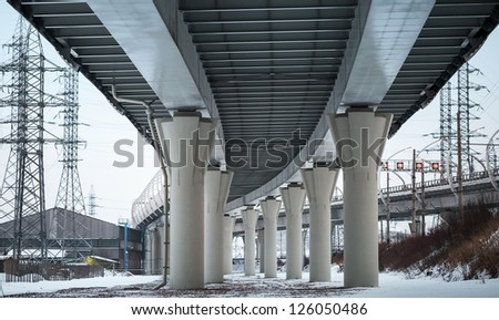 Urban scene with bottom view of steel automotive bridge - stock photo