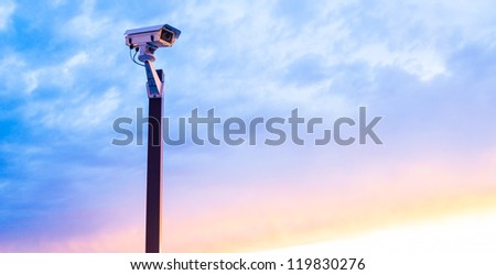 Urban security video camera outdoors at sunset - stock photo