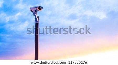 Urban security video camera outdoors at sunset - stock photo