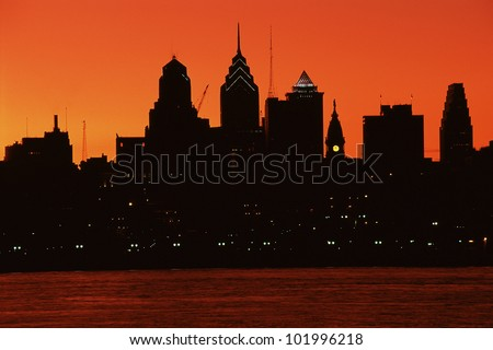 Urban skyline silhouetted by sunset