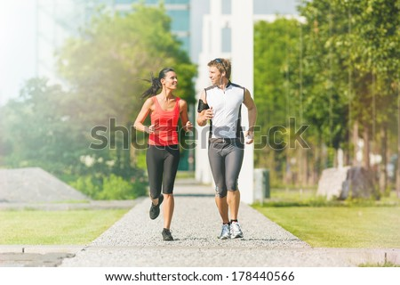 Urban sports - couple running or jogging for fitness in the city on beautiful summer day - stock photo