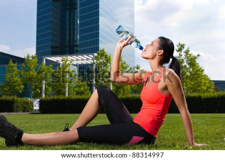 Urban sports - fitness in the city on a beautiful summer day; a woman is drinking water - stock photo