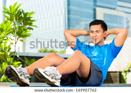 Urban sports - young Asian Indonesian man is doing warming up and sit-ups before running in the city on a beautiful summer day - stock photo