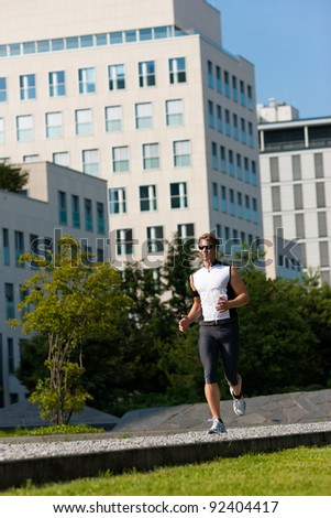 Urban sports - young man jogging for fitness in the city on a beautiful summer day