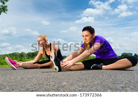 Urban sports - young women doing stretching exercises together before running in the greenfield on a summer day - stock photo