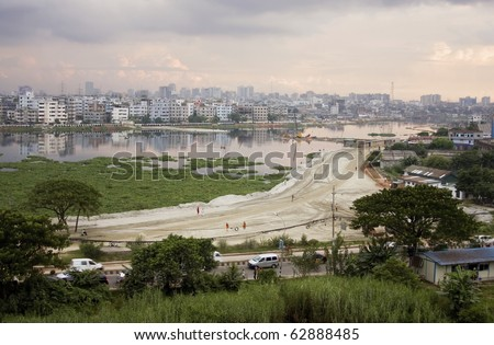 Urban Sprawl: a lake is gradually being filled up for building construction in capital city Dhaka, Bangladesh - stock photo