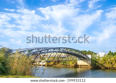 Urban steel bridge over the small river - stock photo