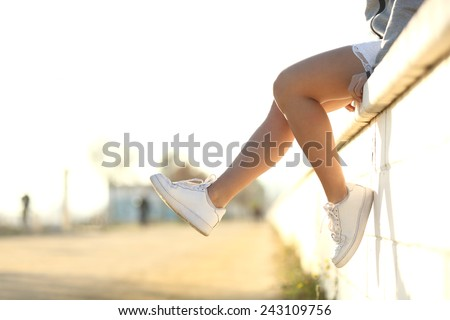 Urban teenager legs silhouette wearing sneakers sitting on a wall - stock photo