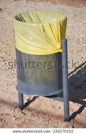 Urban trash can with a yellow bag. Street furniture - stock photo