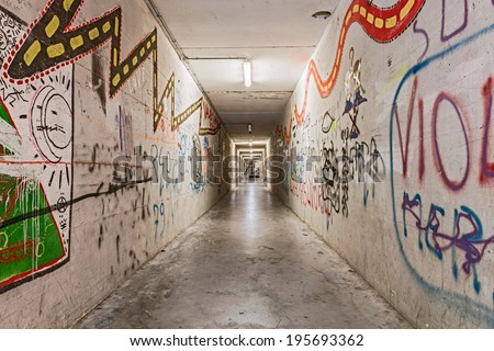 urban underground tunnel with graffiti - light and shadows on grunge pedestrian underpass - dark narrow subway alley  - stock photo