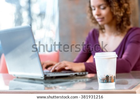 Urban vibes. Selective focus on a paper cup on the table young African female student studying on her laptop - stock photo