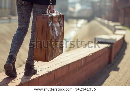 Urban young girl, walking down the street and carrying suitcase - stock photo