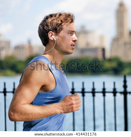 Urban young man running in city park listening to music with wireless in-ear earphones living a healthy active lifestyle. Male runner blue top working out cardio exercise workout in summer.