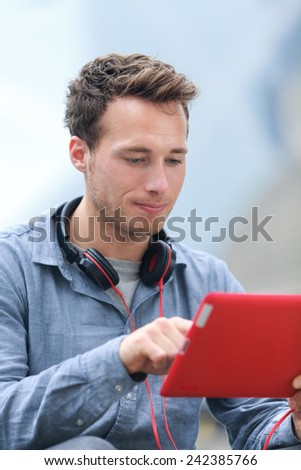 Urban young professional man using tablet computer sitting outside using app on 4g wireless device wearing headphones. Casual young urban professional male in his late 20s. - stock photo