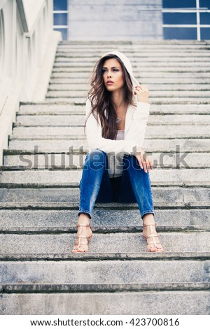 urban young woman sit on stairs in blue jeans high heel sandals and white sweater with hood full body shot - stock photo