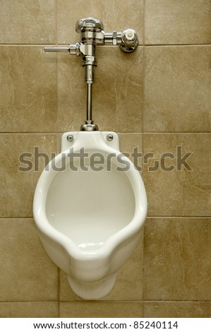 urinal on a marble tiled wall in a men's restroom - stock photo
