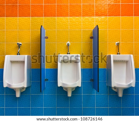 Urinals on colorful wall in public toilet - stock photo