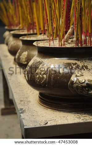 Urns in a Buddhist temple filled with incense and larger prayer sticks - Saigon Vietnam  - stock photo
