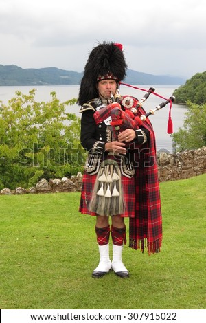 URQUHART CASTLE, SCOTLAND, UK - CIRCA AUGUST 2015: Scottish bagpiper dressed in traditional red and black tartan dress - stock photo