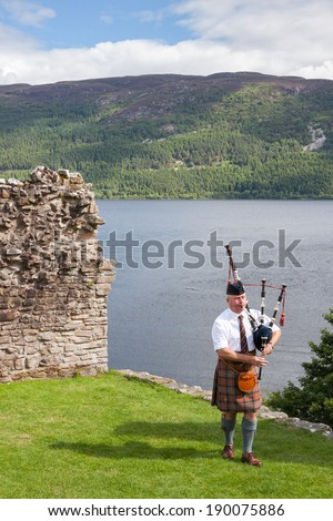 URQUHART CASTLE, UNITED KINGDOM - AUGUST 13: Scottish Highlander wearing kilt and playing Bagpipe at Urquhart Castle, on August 13, 2013. The Castle sits beside Loch Ness in the Highlands of Scotland. - stock photo