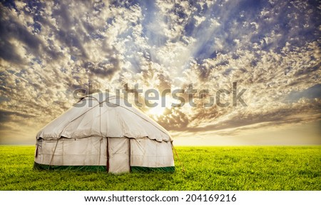 Urta nomadic house on the grass field at sunset evening sky in central Asia