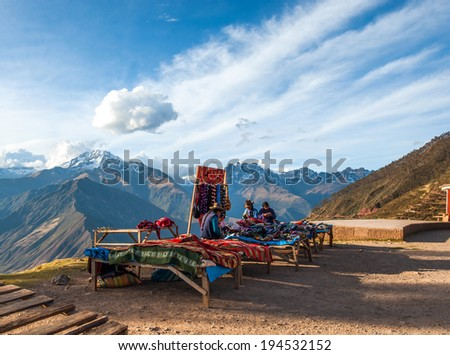 URUBAMBA, PERU - AUGUST 3, 2011: Indian women in national clothes sells the products of her weaving in the tourist spot of Sacred Valley on the road from Cuzco - August 3, 2011 in Urubamba, Peru - stock photo