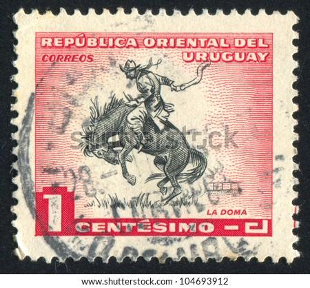 URUGUAY - CIRCA 1954: stamp printed by Uruguay, shows Horse Breaking, circa 1954 - stock photo