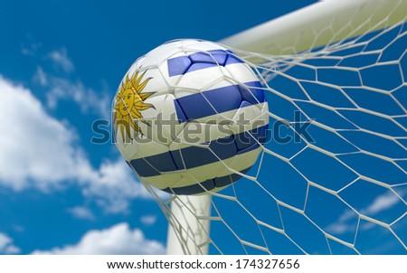 Uruguay flag and soccer ball, football in goal net - stock photo