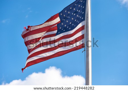 US American flag waving in the wind against blue sky and clouds