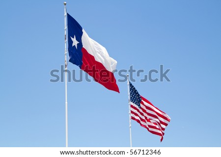 US and Texas flags against blue sky - stock photo
